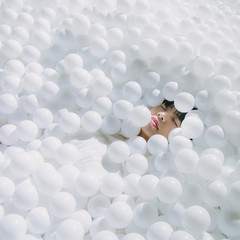 High angle view of woman sleeping amidst balls