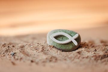Kommunion, Konfirmation, Firmung, Taufe - weißer Fisch aus Holz auf grün bemalten Stein im Sand