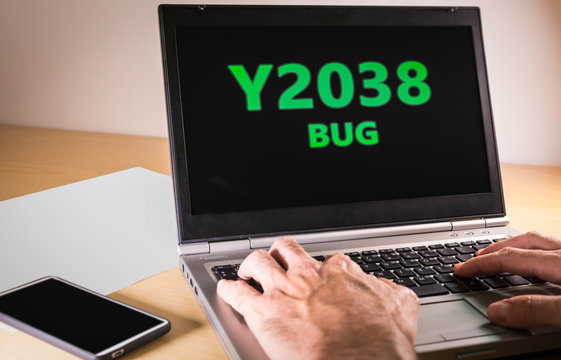 Man hands typing on a laptop in text code. Problem Y2038 concept, also called, year 2038 bug or Unix Y2K. On january 19, 2038 many computers will encounter a date-related bug