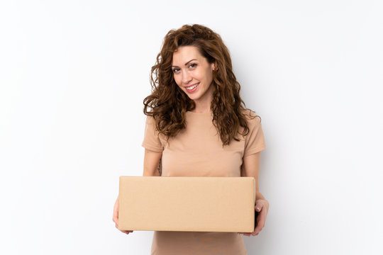 Young pretty woman over isolated background holding a box to move it to another site