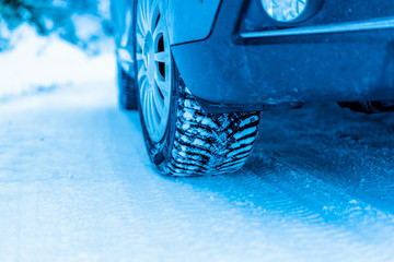 Winter tire on a vehicle on a snowy surface. Close-up