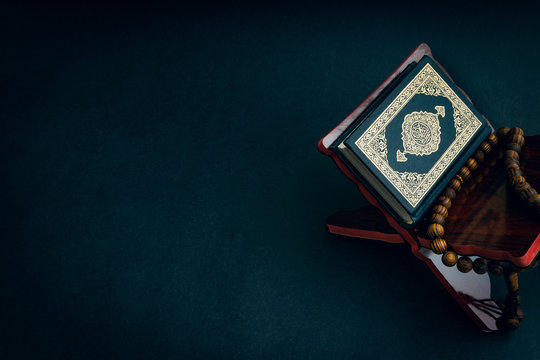 Holy Al Quran with written arabic calligraphy meaning of Al Quran and tasbih or rosary beads on black background. Selective focus and crop fragment