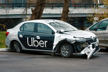 Minsk, Belarus - Nov 2019. Damaged car of Uber taxi service at the parked zone after car accident on the road.  Wrecked taxi car after a head-on collision in a parking lot