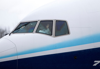 A pilot waves as a Boeing 777X airplane taxis during an attempted first test flight from the company's plant in Everett