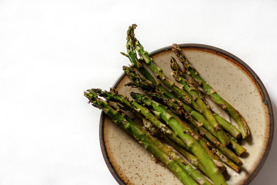 Roasted asparagus beautifully lying on a brown plate on a light background. Partly visible, closeup.