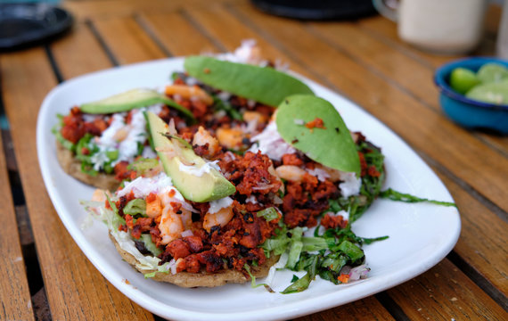 Mexican tostada with topping of minced sausage and shrimp, with avocado on top, on a white plate