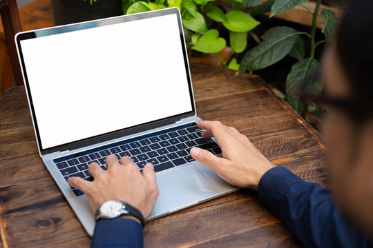 mockup image blank screen computer with blank white background for advertising text,hand man using laptop contact business search information on desk at home office.marketing and creative design