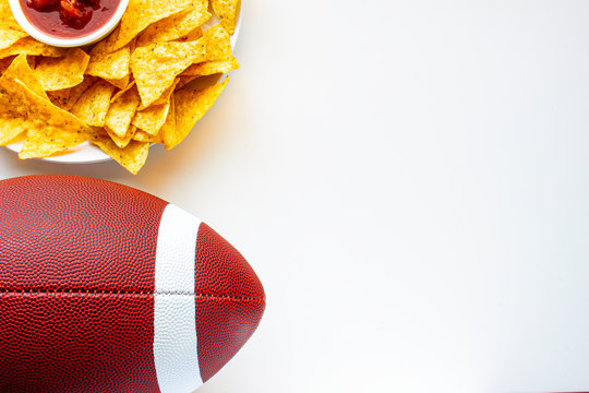 An American football with organic nacho chips and mild salsa on the side on a white background
