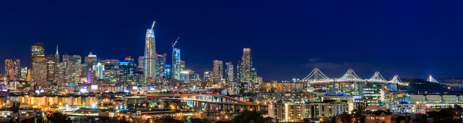 San Francisco skyline night panorama with city lights, the Bay Bridge and trail lights