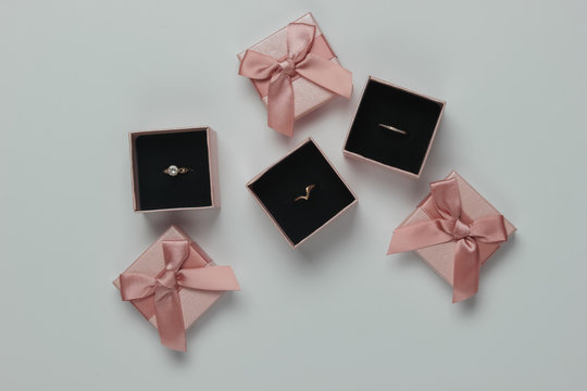 Gold rings in gift boxes on white background. Jewelry shop. Top view