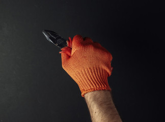 Hands with work gloves are holding pliers on black background. Industrial worker