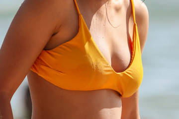 The chest of a girl in a yellow swimsuit