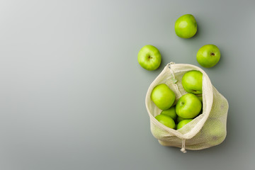 Green apples in a reusable white cotton bag on a gray background.