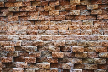 Rough brick wall with uneven offset bricks