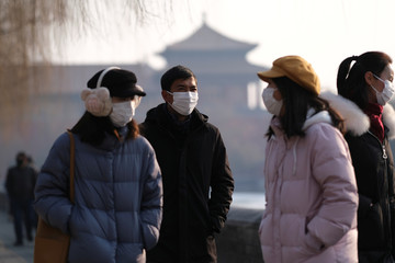 People wearing protective masks walk outside Forbidden City which is closed to visitors, according to a notice in its main entrance for the safety concern following the outbreak of a new coronavirus, in Beijing