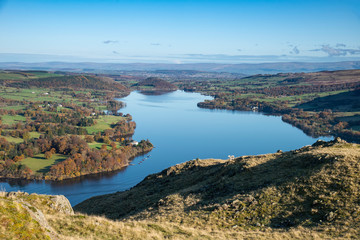 Fotobehang Blauw Beautiful Autumn Fall landscape of Ullswater and surrounding mountains and hills viewed from Hallin Fell on a crisp cold morning with majestic sunlgiht on the hillsides