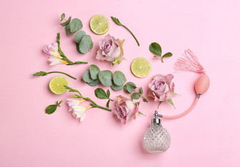Beautiful flat lay composition with bottle of perfume, lime, eucalyptus and flowers on pink background Wall mural