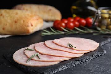 Slices of tasty ham on black table, closeup