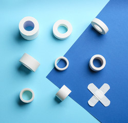 Different types of sticking plasters on blue background, flat lay