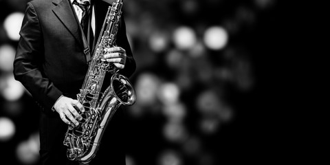 Playin' sax isolated at the left border of a black background (black and white)