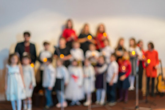 Children's choir on stage. Young talents. Children's performance. Blurry