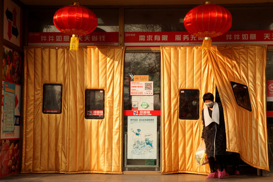 A woman wearing a face mask leaves a supermarket decorated with Chinese New Year lanterns in Beijing