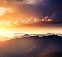 Wall Mural - Alpine mountains are illuminated by the sunset. Picture of colorful cloudy sky.