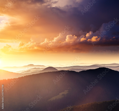 Wall mural Alpine mountains are illuminated by the sunset. Picture of colorful cloudy sky.