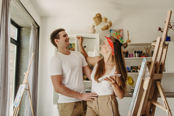 Love story of a beautiful couple in an art studio. They paint pictures, laugh, kiss each other. Their emotions, feelings, love.