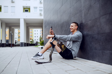 Fotomurales - Young smiling positive handsome caucasian sportsman with artificial leg sitting on ground, leaning on the wall, listening music and texting on smart phone.