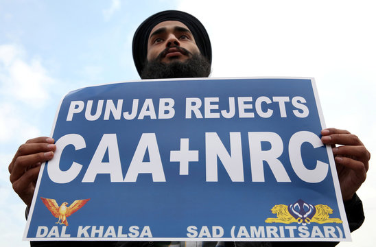 A demonstrator displays a placard during a protest against a new citizenship law, in Amritsar