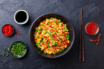 Asian fried rice with egg and vegetables. Dark stone background. Top view.