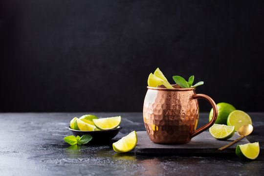 Cold Moscow Mules cocktail with ginger beer, vodka, lime and mint. Grey stone background. Copy space.