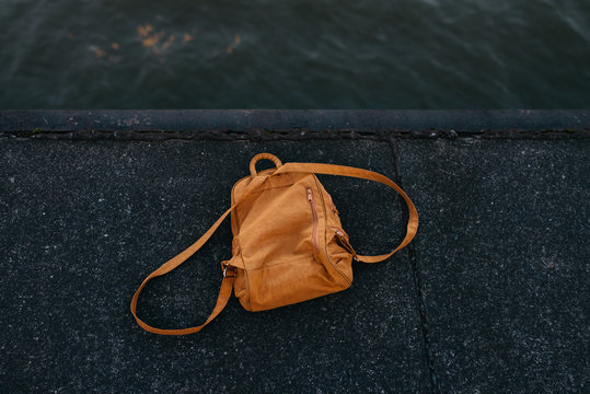 High Angle View Of Brown Backpack On Pier Over Lake