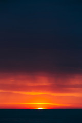 Natural Colorful Sunset Sunrise Sky Over Sea After Storm Rain. Seascape With Shining Setting Sun On Sea Horizon