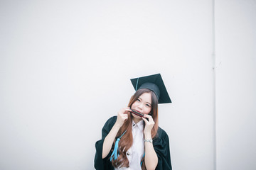 PORTRAIT OF YOUNG WOMAN IN graduation gown playing harmonica