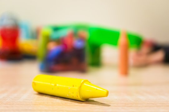 Closeup shot of a yellow crayon on a wooden surface