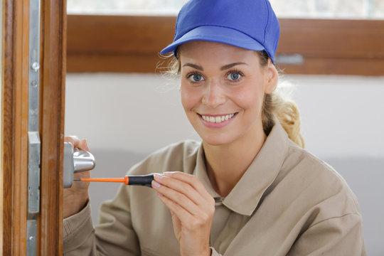 portrait of young woman fixing door with screwdriver