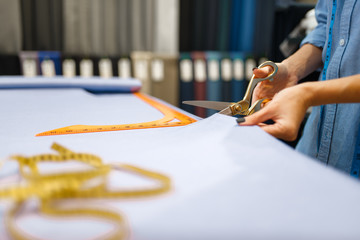 Seamstress cuts fabric with scissors in store