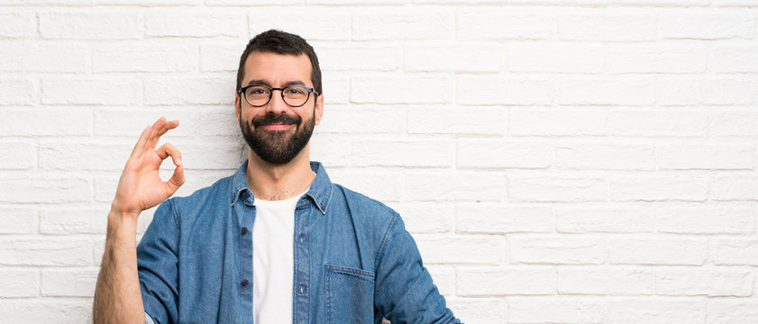 Handsome man with beard over white brick wall showing ok sign with fingers