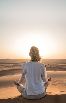 REAR VIEW OF WOMAN SITTING ON SAND IN DESERT