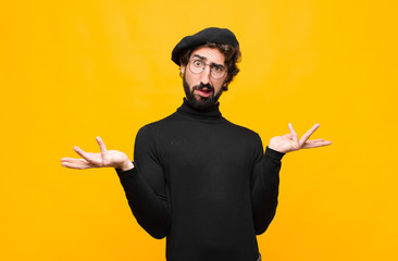 young french artist man shrugging with a dumb, crazy, confused, puzzled expression, feeling annoyed and clueless against orange wall