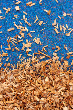 Coverage on the playground. Yellow-brown wood chips and a bright blue soft rubber coating. Vertical.