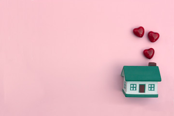 A small house, red hearts fly out of the pipe on a pink background. The concept of happiness, love in your home, buying, selling, renting a property, mortgage
