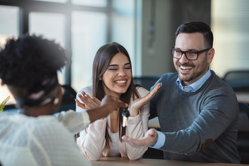 Young happy couple receiving house keys from real estate agent. Giving keys of new house to young couple. Smiling couple signing financial contract for mortgage. Real estate agent handing over the key