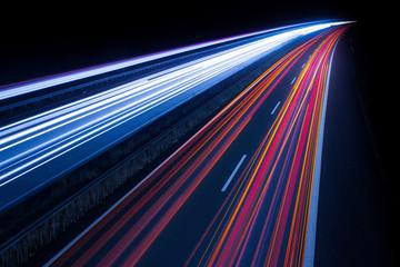 LIGHT TRAILS ON ILLUMINATED CITY ROAD AT NIGHT