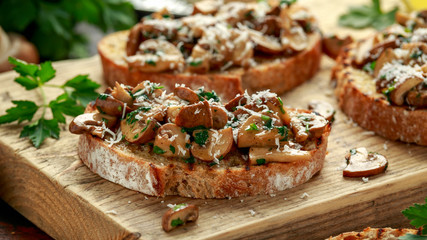 Grilled mushroom toast with parsley, lemon and parmesan cheese on wooden board. healthy vegan food