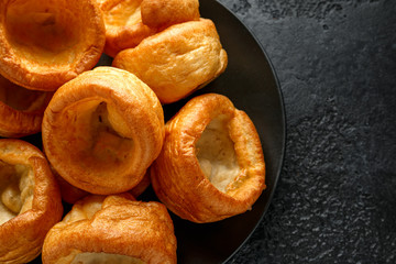 Traditional English Yorkshire pudding side dish on black plate and background