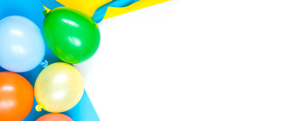Colorful balloons located on the left side of the image on a classic blue background. Greeting card. Flat lay style. Copyspace for text.