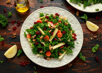 Kale salad with dried cranberry, carrots, walnuts and apple. healthy vegan food.